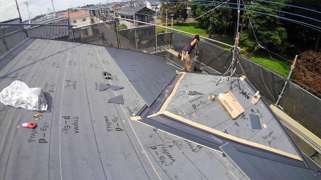 ガルバリウム鋼板の屋根材を設置している様子
